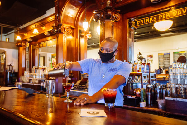 bar photography of bartender pouting drink at headframe spirits in butte montana