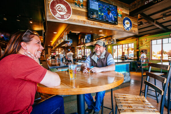 restaurant photography of couple enjoying a beer at mackenzie river pizza co in butte montana