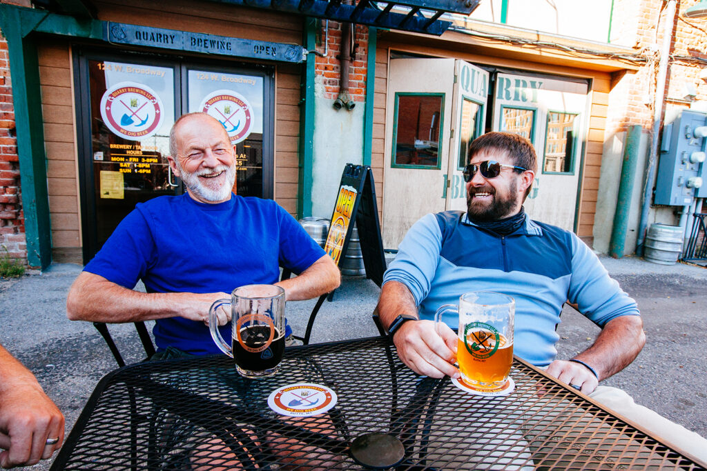 brewery photography of two men enjoying a beer outside of quarry brewing in butte montana