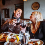 restaurant photography of two girls laughing at la casa toscana in butte montana