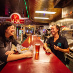 restaurant photography of two girls laughing at m&m bar and cafe in butte montana