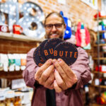 retail photography of store owner holding butte montana themed pins