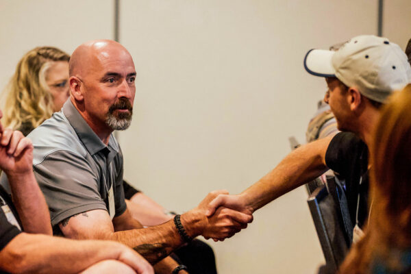 event photography of two men shaking hands at safe schools summit in butte montana